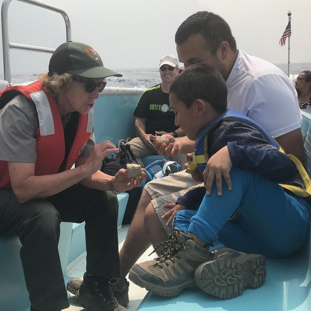 During a boat tour, ranger talks with visitors.
