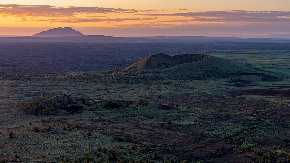 Sunrise view of Crescent Butte with Big Southern Butte on the horizon.