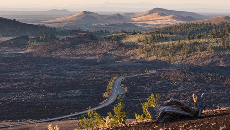 A panoramic shot of a volcanic landscape with a road running through it.