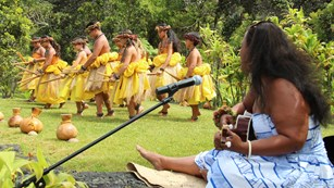 Woman singing to a line of hula dancers