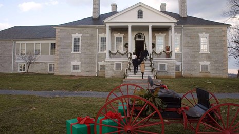 Sleigh with wrapped presents in front of a historic mansion
