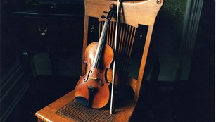 Violin resting on back of chair in darkened room