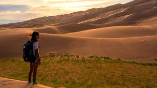 Kid with a backpack standing near sand dunes at dusk