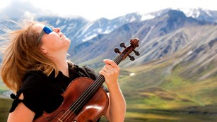 Woman with a string instrument in a mountainous area
