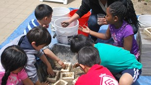 Kids making adobe bricks