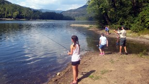 Small group of girls fishing on a riverbank