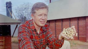Historical photo of Jimmy Carter on a farm holding a handful of peanuts