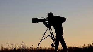Silhouette of photographer with large lens camera
