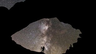 Siloutte of a photographer standing under a geological arch with a star-filled sky in the background