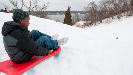 Kid perched to sled down a hill