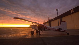 Plane outside of a hangar during sunset