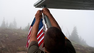 Volunteer handing a US flag on a porch