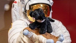 Astronaut holding a small black plush dog