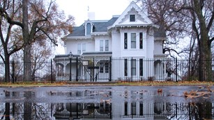 Three-story white house and reflection in a pond