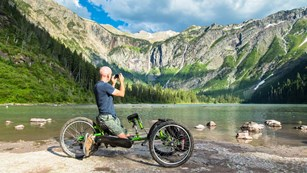 Man in wheelchair along edge of lake taking picture of mountain scene