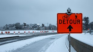 Detour sign in front of snow and ice covered road