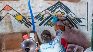 Conservationist working on Native American artwork on a wall