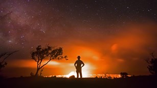 Silhouette of a ranger in front of a lava eruption, trees, and night sky