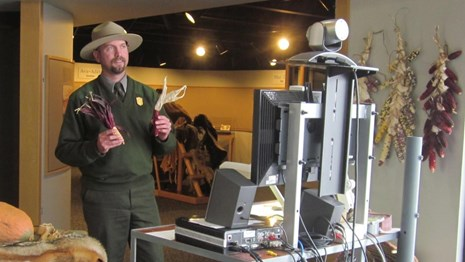 Ranger holding props in front of a computer camera