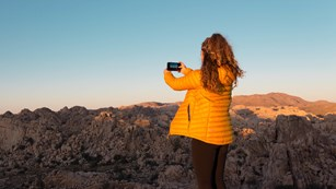 Visitor taking a picture of a desert canyon at sunset