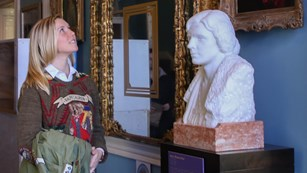 Visitor looking at a bust and paintings of suffragists