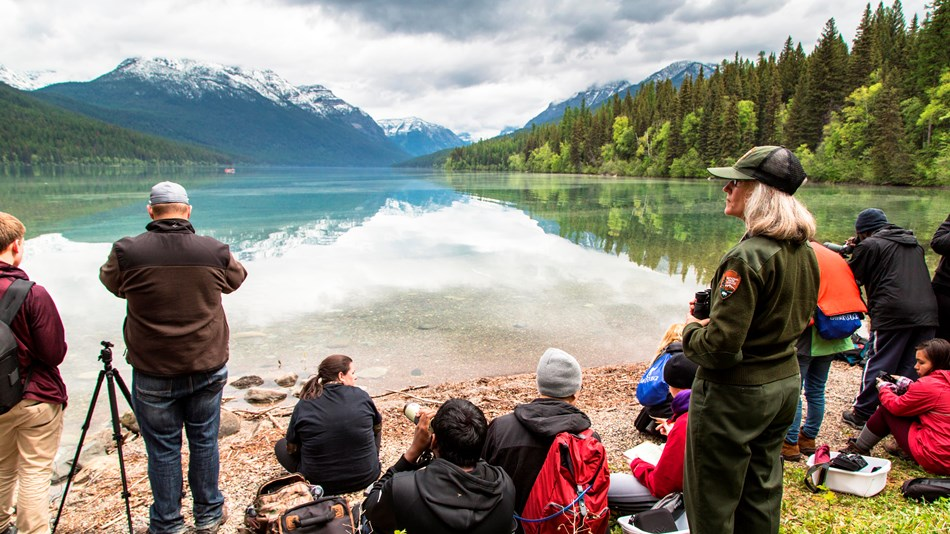 Group of students with ranger sit looking for loons at Bowman Lake