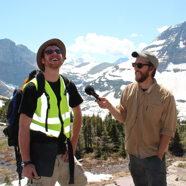 A young man uses a microphone to interview a researcher wearing a safety vest.