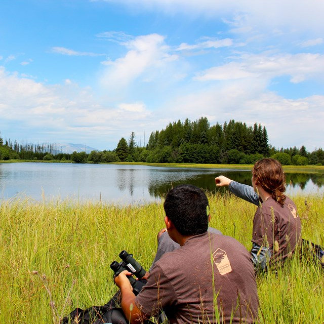 Two high school students sit in tall grass near edge of lake; one points toward lake.