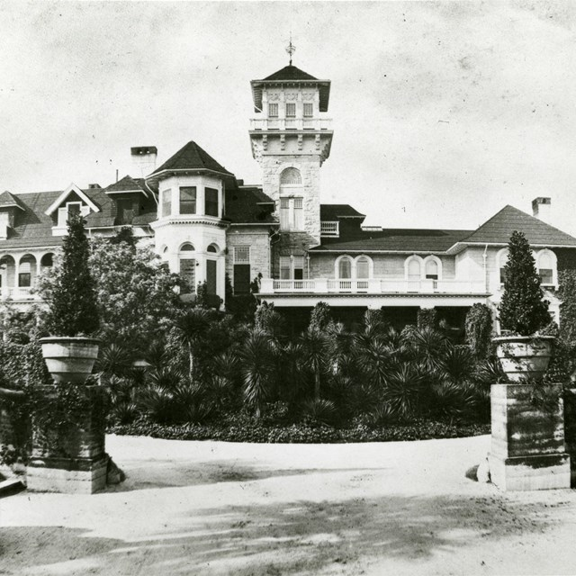 view of large mansion with tower and gardens