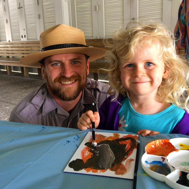 Ranger and little girl work on painting an art project