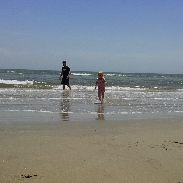 Man and young girl play in the surf on the beach