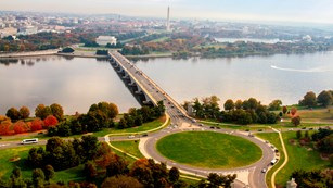 Cars move around a traffic circle and bridge over a river, toward a city with trees and monuments