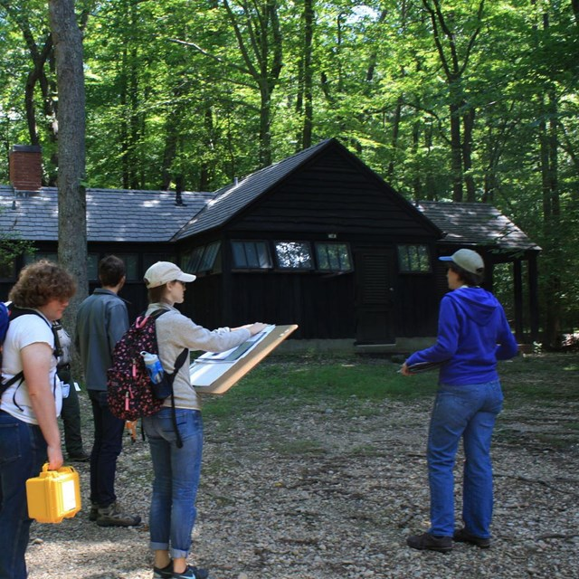 A group of people with documentation gear and site plans stand in a wooded area beside a cabin