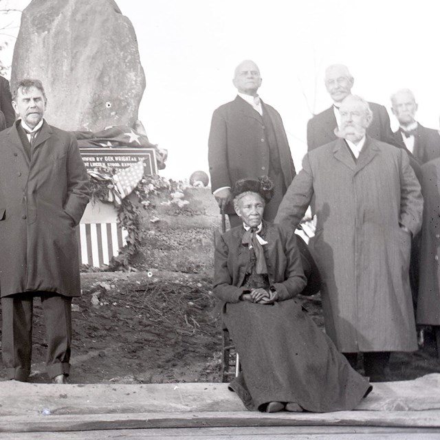 Elizabeth Thomas, seated, with Civil War Veterans beside a stone monument at Fort Stevens, 1911