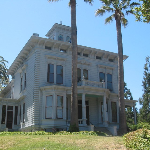 A rectilinear two-story house in a sunny location, beside palm trees, John Muir NHS.