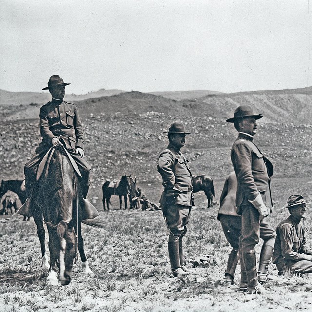 Soldiers in uniform and flathats gather in a field at Yellowstone, one on a horse.