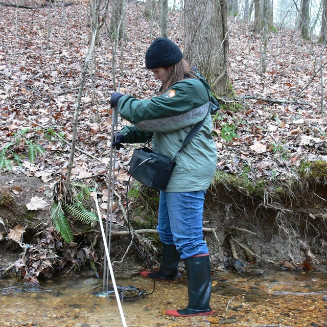 Network biologist Brenda Wells measures stream discharge at Shiloh National Military Park.
