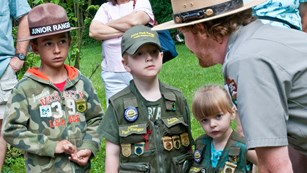 A uniformed ranger speaks to three children in green vests covered in Junior Ranger badges
