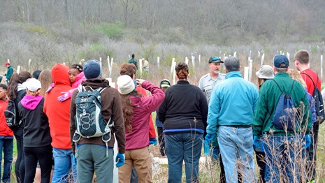 volunteers gathering in a field to work on Earth Day