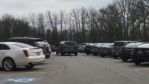 A gray minivan navigates a crowded parking lot