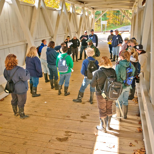 A group of educators stands inside the Everett Covered Bridge, listening to a ranger
