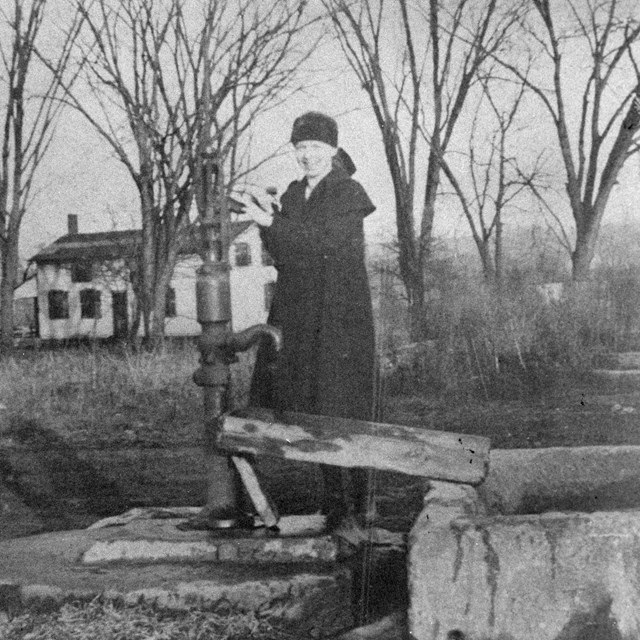 A black-and-white photo of a woman in a long, black dress standing at a water pump.