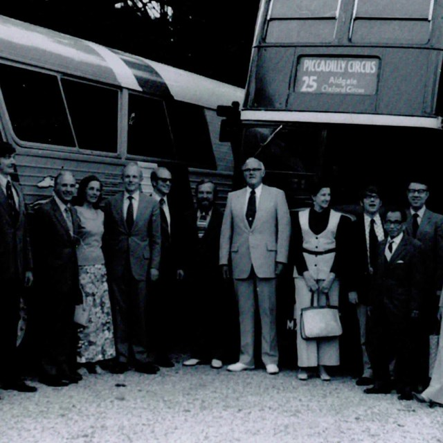 A black-and-white photo of twenty people, mostly men dressed in suits; behind them, two tour buses.
