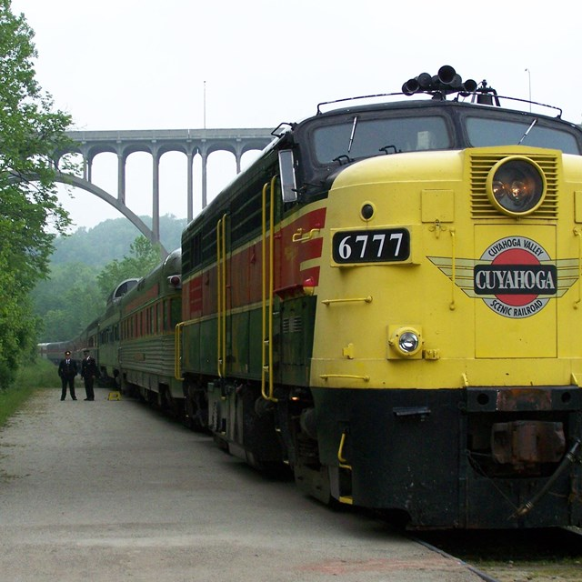 A train painted black, red and yellow stretches into the distance, where an arched bridge rises.