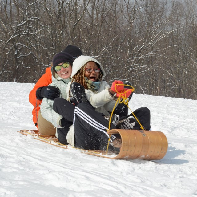 Three adults sledding together on Kendall Hills