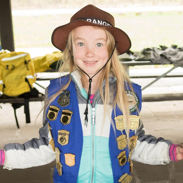 A girl wearing a brown Junior Ranger hat and a blue vest covered in badges smiles at the camera