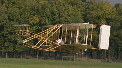 A replica Wright brothers plane flies low to the ground with trees in the background