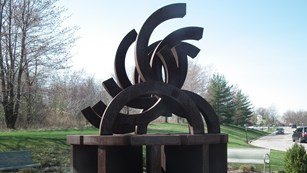 The memorial sculpture depicts broken Olympic rings.