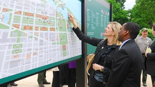 A woman points on a large outdoor map.