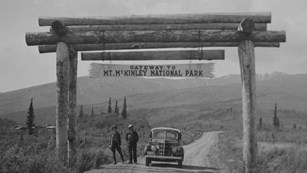 historic photo of people standing under a sign for the Mt. McKinley National Park